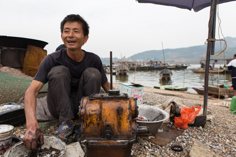 Young-Lin-cleans-his-engine-near-his-boat-in-Datang.jpg